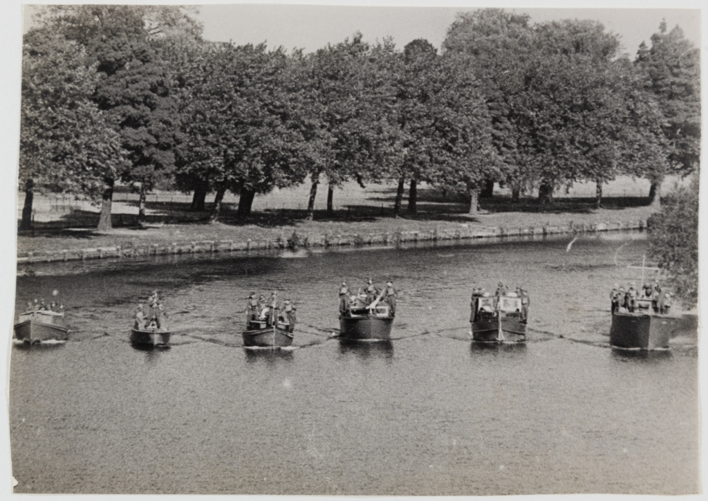 Black and white photograph of six small boats in a row on the Thames, carrying several passengers. In the background there is a row of trees at the water's edge.