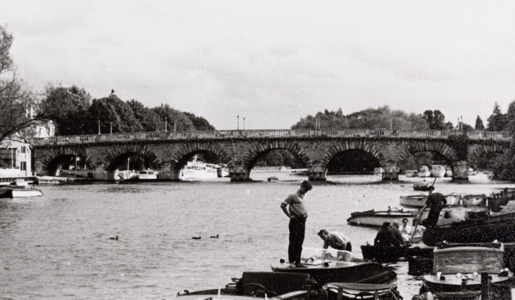 Black and white photograph of small boats on the Thames with some people in them and a large bridge in the background. In the foreground, one man is stood on the front of the boat, looking down at it.