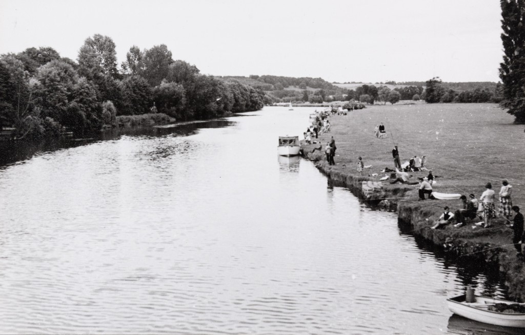 Black and white photograph of groups of visitors lining the Thames riverside at Pangbourne.