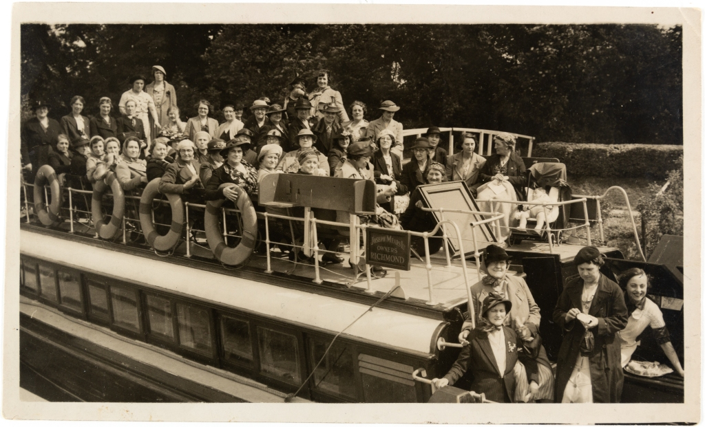 Black and whitephotograph ofgroup of women and one baby sat on the top deck of a steamboat, sign reads: Joseph Mears Ltd, owners, Richmond.