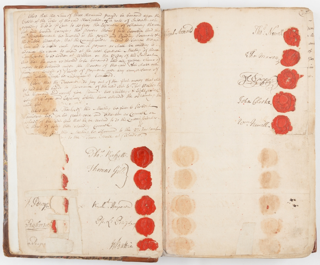 Colour photograph of two pages of a minute book featuring the conclusion of the first meeting of the Thames Navigation Commission with signatures and red seals.
