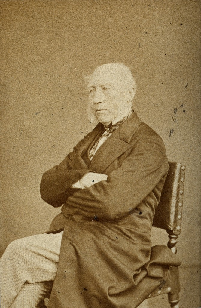 Sepia photograph of Professor John Phillips dressed in smart attire and sat on a chair with folded arms, looking away from the camera.