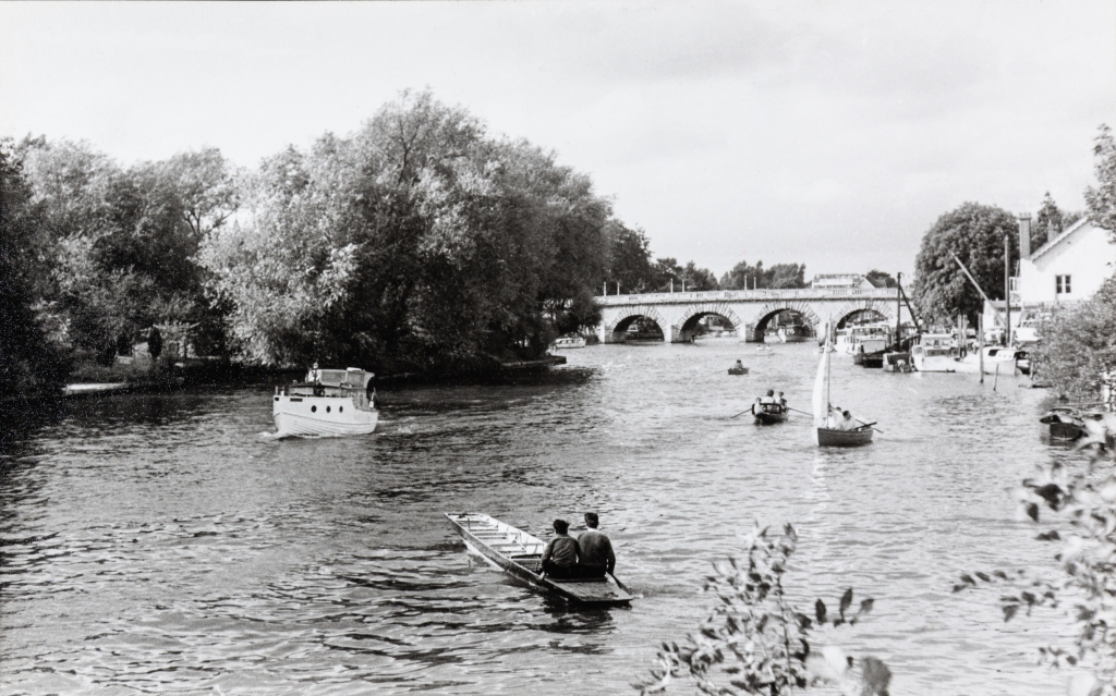 Black and white photograph of boats on the River Thames with an arched bridge in the background. In the foreground is a long wooden paddle boat with two boys sat side by side at the back. There is also a small motorised boat and other paddle boats on the river.