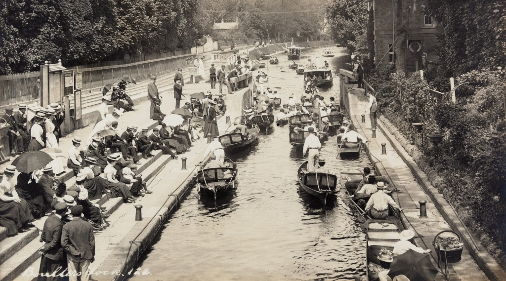 Black and white photograph of a crowd of men and women in Edwardian dress stood or sitting on the steps next to the riverside and small boats on the Thames.
