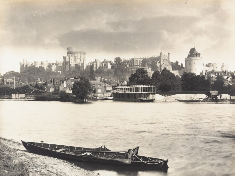 Black and white photograph of the River Thames with Windsor Castle in the background. A long wooden paddle boat is in the foreground. A large river cruiser is also on the river.