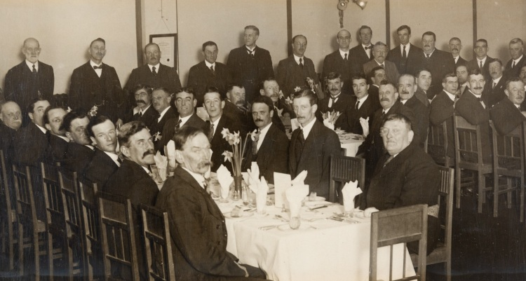 A large group of smartly dressed men looking towards the camera and wearing suits and ties/bow ties. Most are seated at three long dining tables. Some men are stood behind the tables.