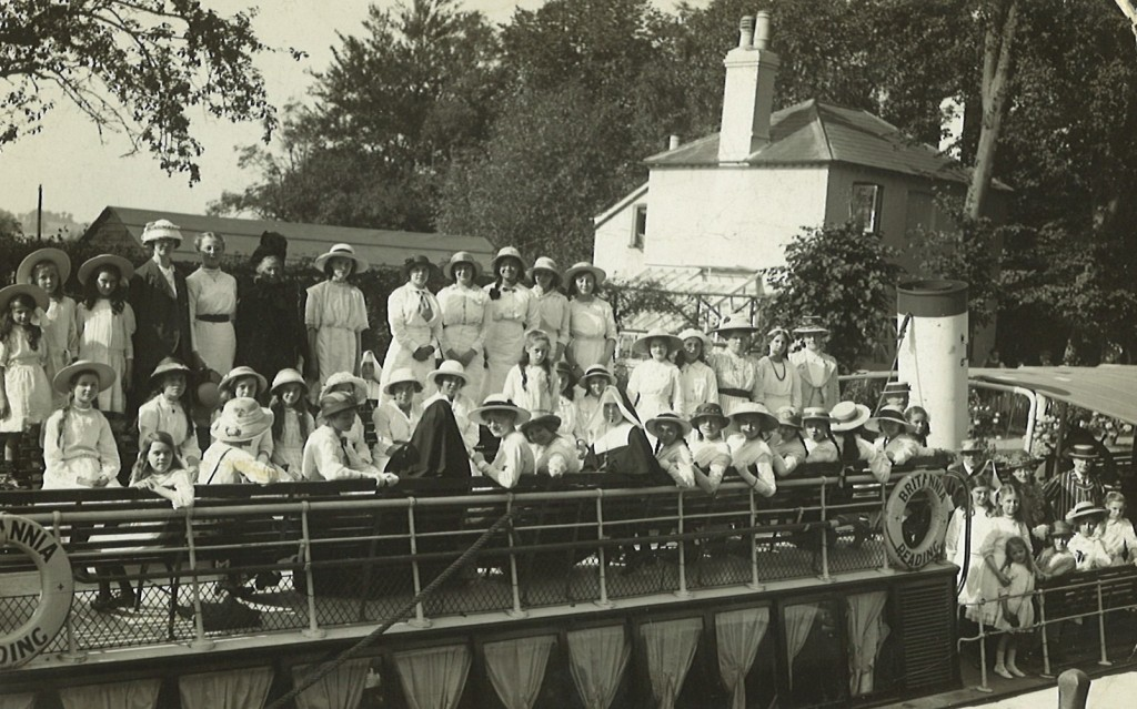 Black and white photograph of a large group of women aboard the Britannia river-boat on the Thames, c.1914. Most women are wearing long white dresses and straw hats. A man at the front of the boat wears a pinstripe suit and boater hat. There are two women wearing nun's clothing. A ring on the side has 'Britannia Reading' printed on it.