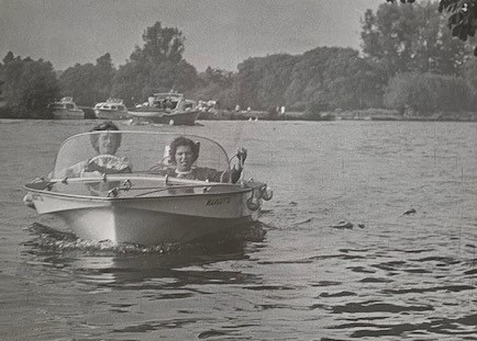 Black and white photograph of two women in a small motor boat on the Thames wearing 1960s clothing. Boats and trees are in the background.