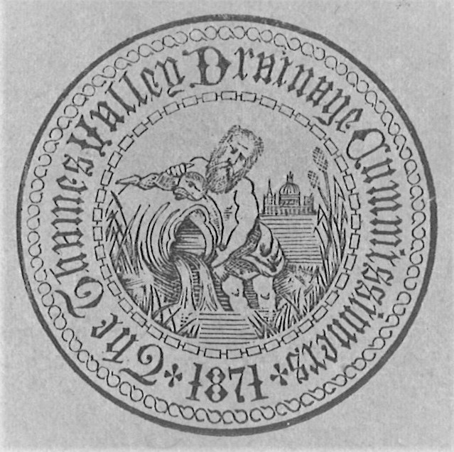 Black and white circular logo with 'The Thames Valley Drainage Commissioners 1871' around the outside edge. In the centre is a bearded man pouring water from a large vessel beside grass in front of an elaborate domed building.