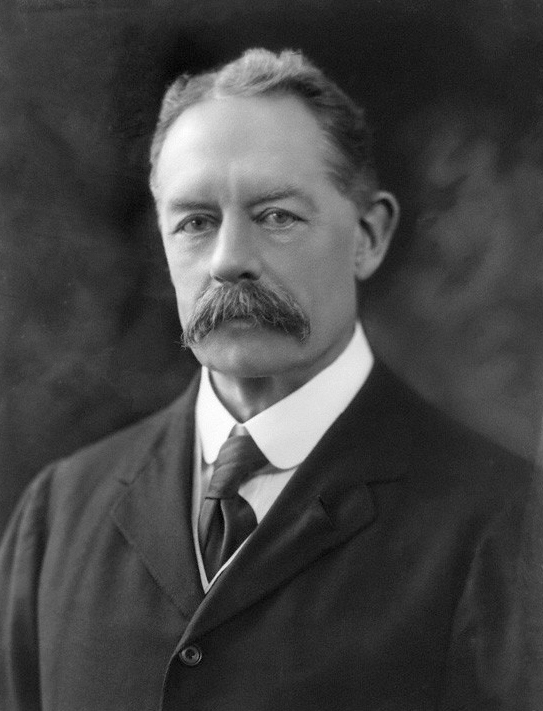 Headshot of a smartly dressed man in his mid 60s with a moustache and parted hair wearing a suit jacket, shirt and tie.