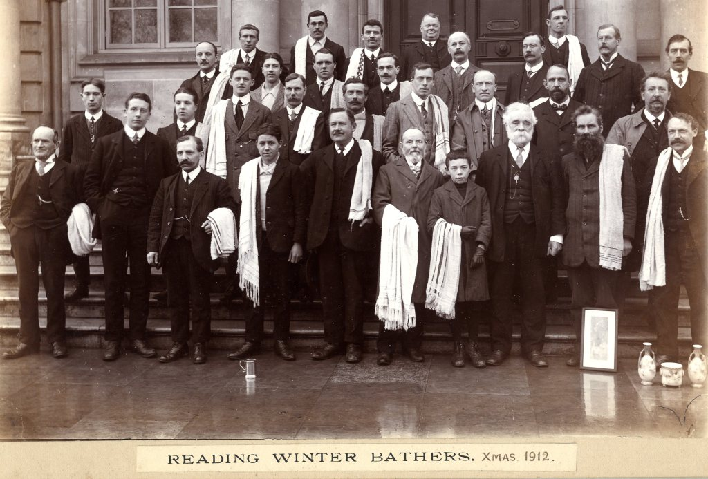 Black and white group photograph of members the Reading Winter Bathers club, all men, some younger boys, dressed in smart attire holding towels. Label reads: Reading Winter Bathers, Xmas 1912.