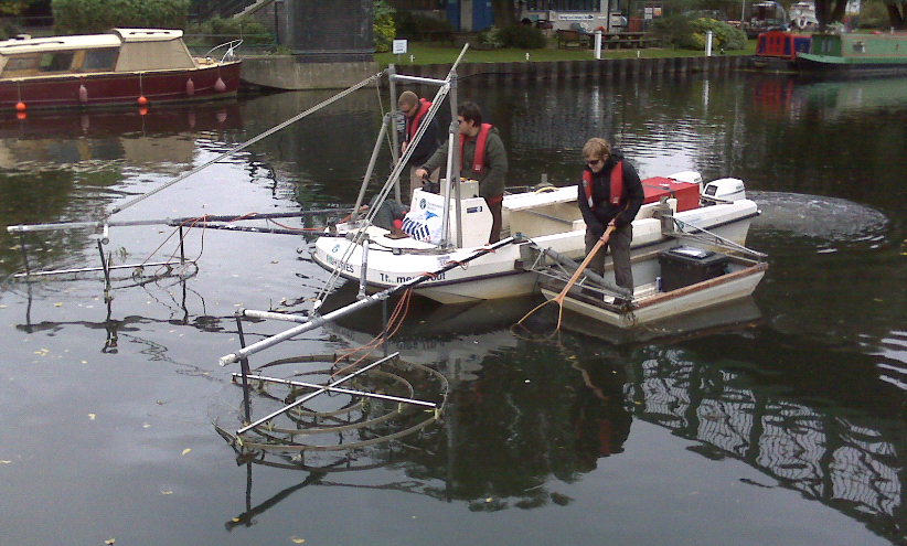 Three Environment Angency employees on a boom boat on the River Thames, one woman employee has a fishing net in the water