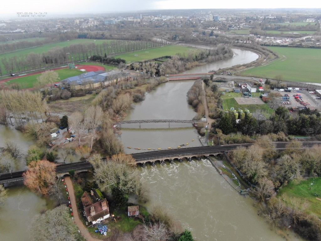 Aerial view of the Jubilee River with a train line going through the centre of the image and a car park on the right and a house on the left