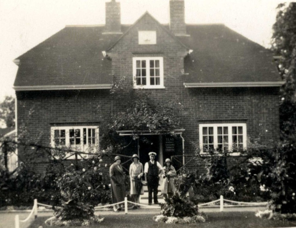 Three women and one man stood in front of a large brick house. The women are wearing woolen coats and cloche hats. The man is wearing a captain's hat.