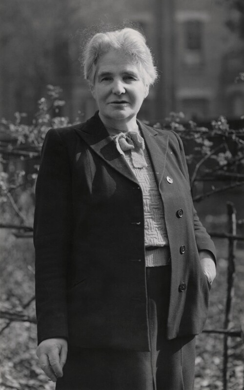 A woman in her late 50s with short white hear wearing a smart jacket, trousers and knitted sweater with a bow at the neck.