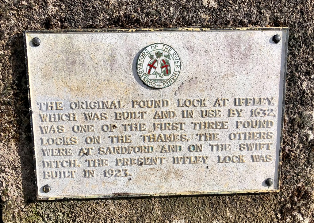 Plaque reads, 'The original pound lock at Iffley, which was built and in use by 1632, was one of the first three pound locks on the Thames. The others were at Sandford and on the swift ditch. The present Iffley Lock was built in 1923'. Text below the logo for the 'Conservators of the River Thames'.