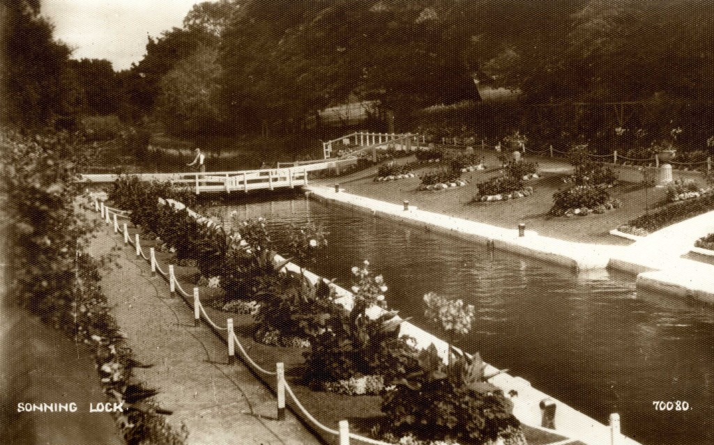 Black and white photograph of a lock with several neatly arranged flower beds on either side and a pathway sectioned off. In the distance, a man is stood on the bridge wearing a waistcoat and flat cap.