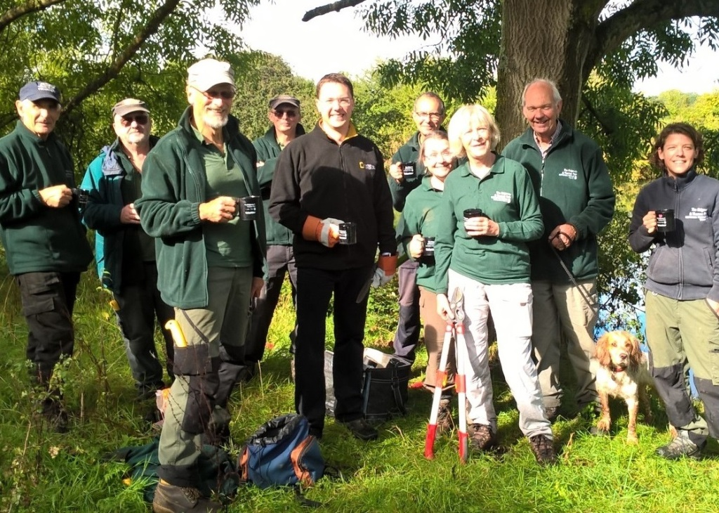 Group photograph of Thames Path volunteers and dog, standing, smiling and holding mugs by the River Thames.