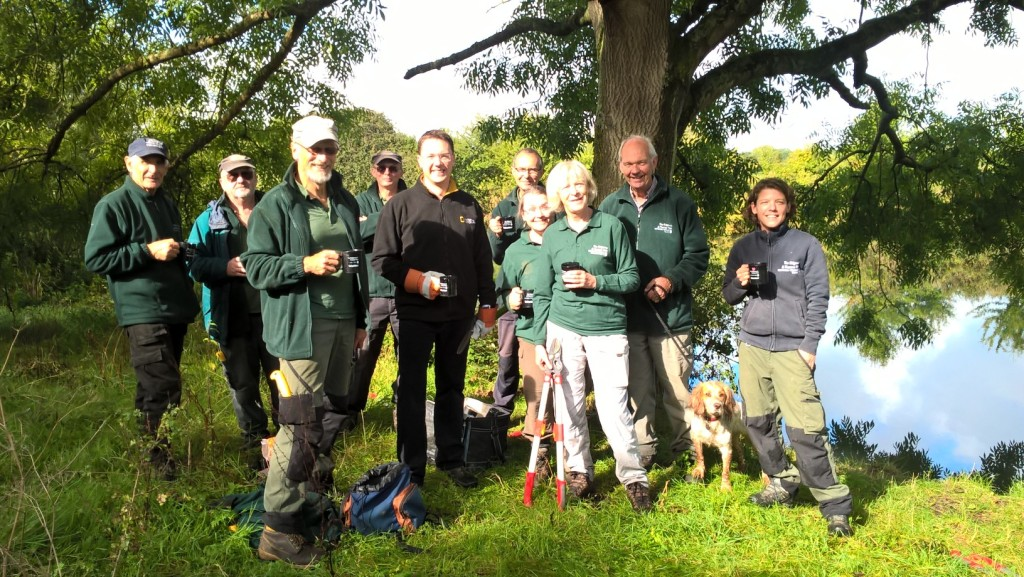 Group photograph of Thames Path volunteers  and dog, standing, smiling and holding mugs by the River Thames