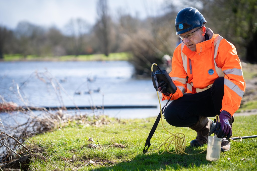 Colour photograph of a Thames Water employee crouching on grass by the River Thames with equipment in- hand
